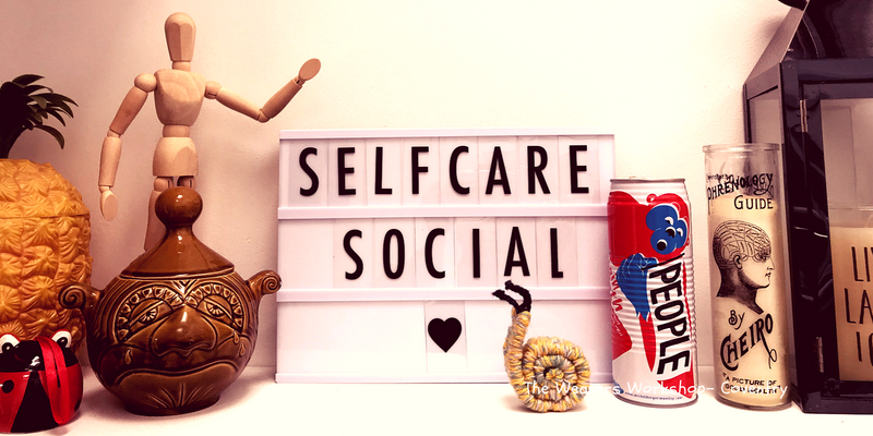Photo of my woven snail on a shelf at Feel Good Hq. There is a sign behind the snail that says Self Care Social.