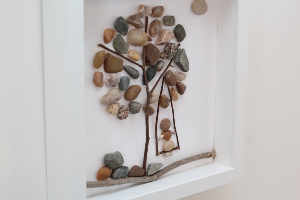 diy pebble art made with pebbles and twigs in a frame