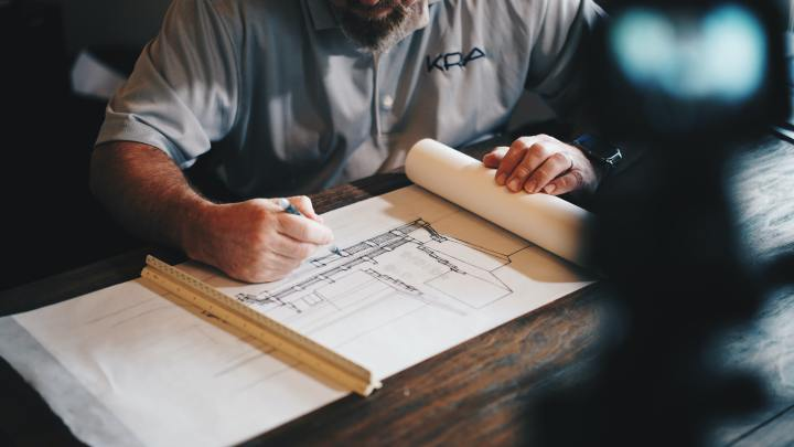 Photo of man working on blueprint drawing