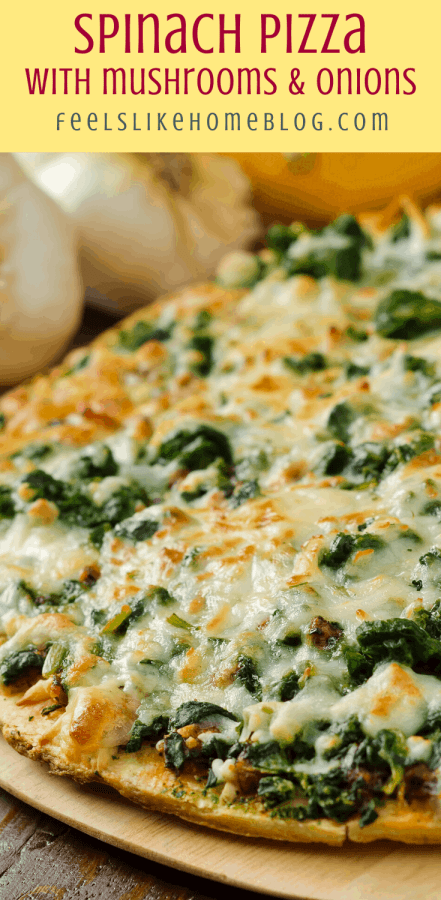 close up of spinach pizza with mushrooms and onions