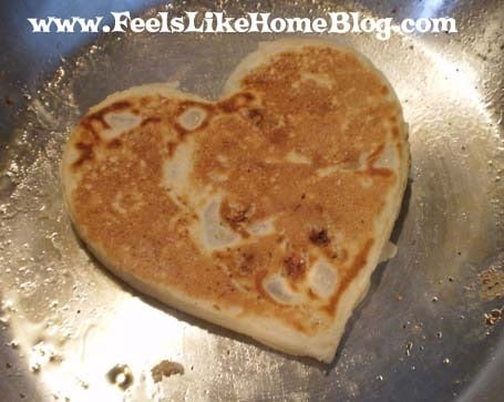 A pancake in a skillet with heart shaped