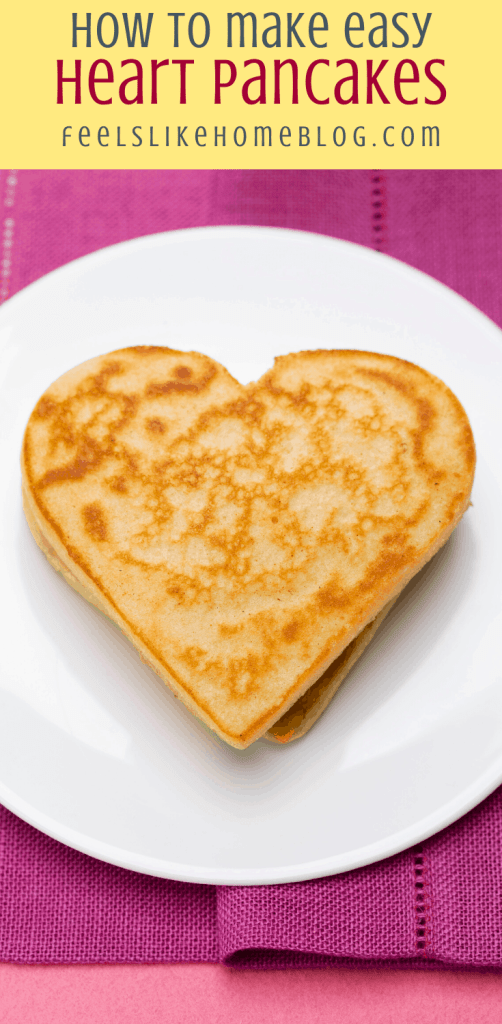 a pancake on a white plate with a pink napkin and hearts