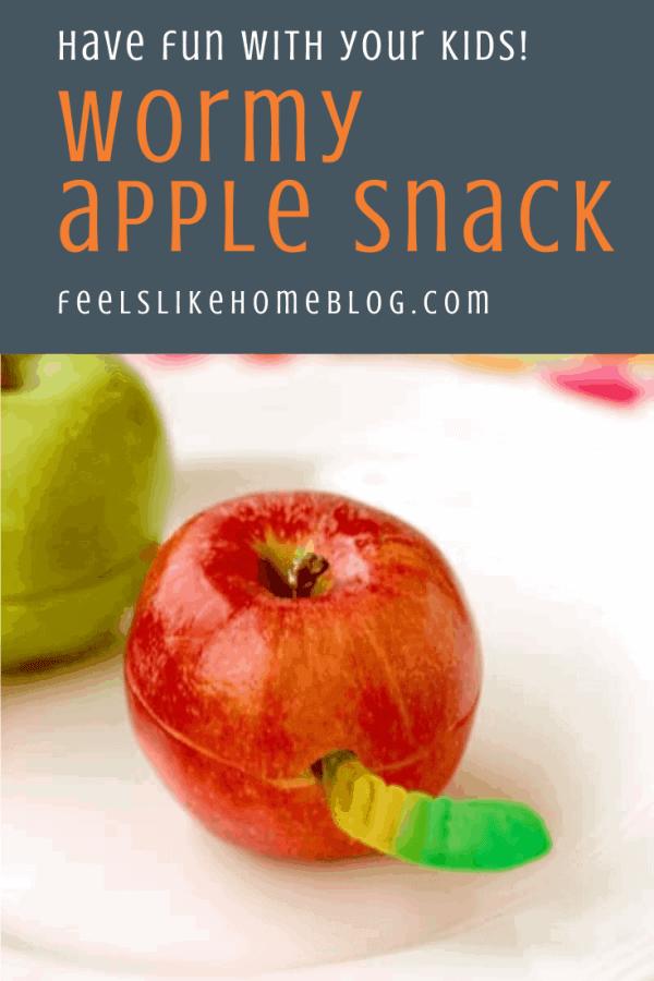 An apple with a gummi worm