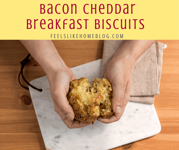 A person splitting a bacon cheddar breakfast biscuit in half