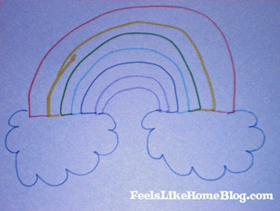 A close up of a rainbow drawn on blue paper