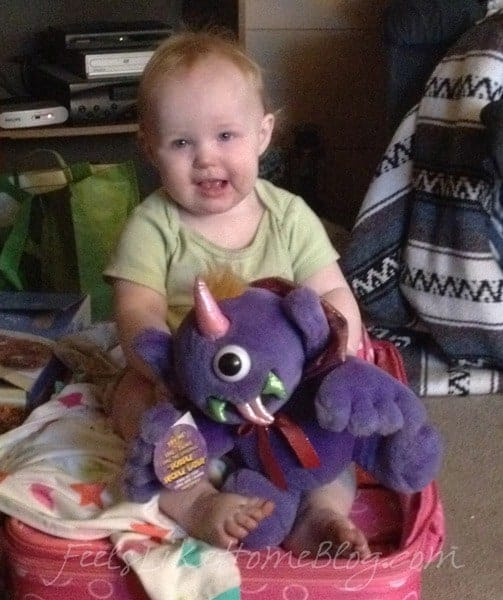 A dirty baby holding the purple people eater stuffed animal