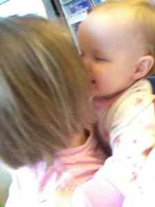 A little girl kissing her baby sister