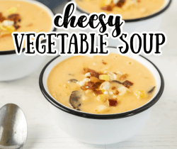 a bowl of creamy vegetable soup topped with bacon and leeks