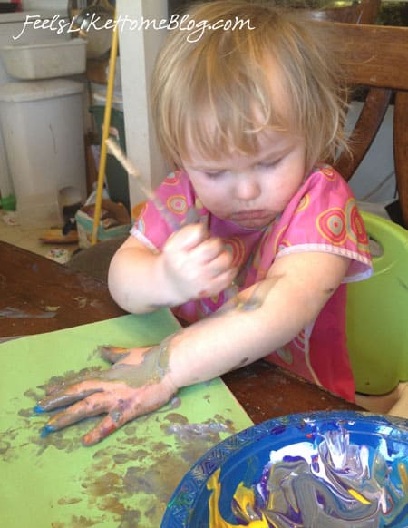 A little girl painting herself