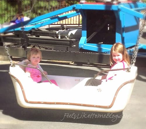 Two little girls sitting in an amusement park ride