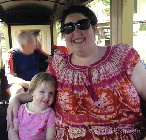 A woman and a little girl posing in a train car at Hersheypark