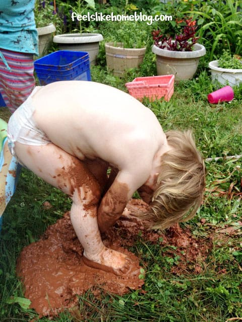 The little girl is now wearing only a diaper and is still covered in mud
