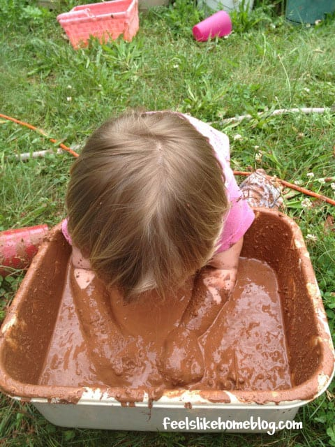 A little girl up to her armpits in mud