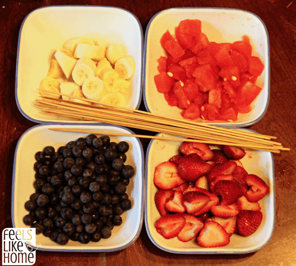 Bowls filled with banana, watermelon, blueberries, and strawberries