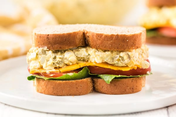 egg salad sandwich with lettuce, tomato, and cheese