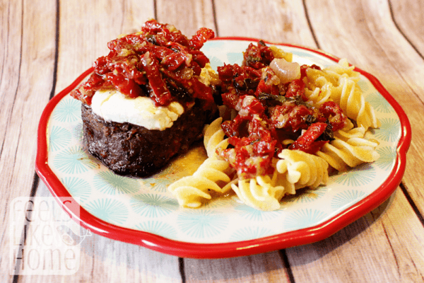 A plate of filet bryan with pasta and sun dried tomatoes