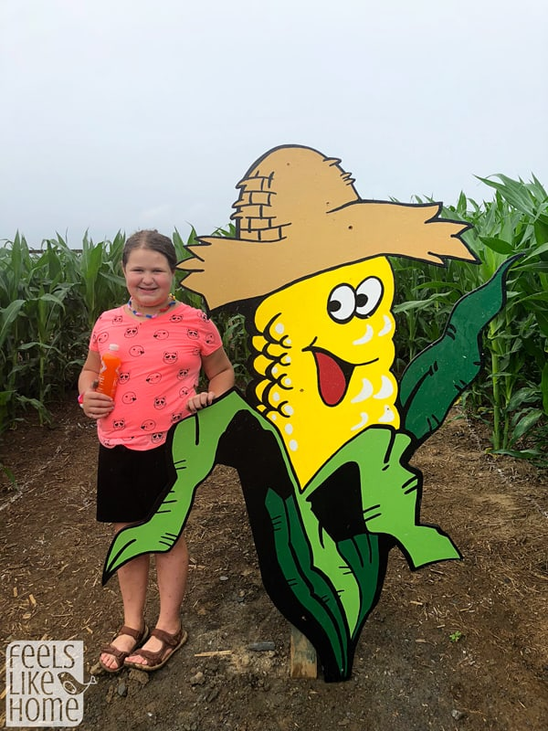 A girl standing in front of a corn cob