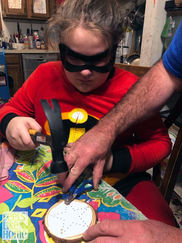 A girl in a superhero costume hammering in nails