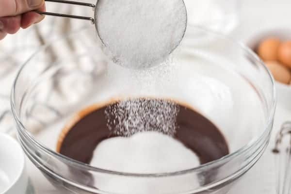 adding sugar to homemade brownie batter