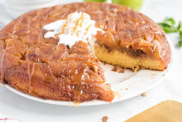 caramel apple upside down cake with whipped cream on a plate