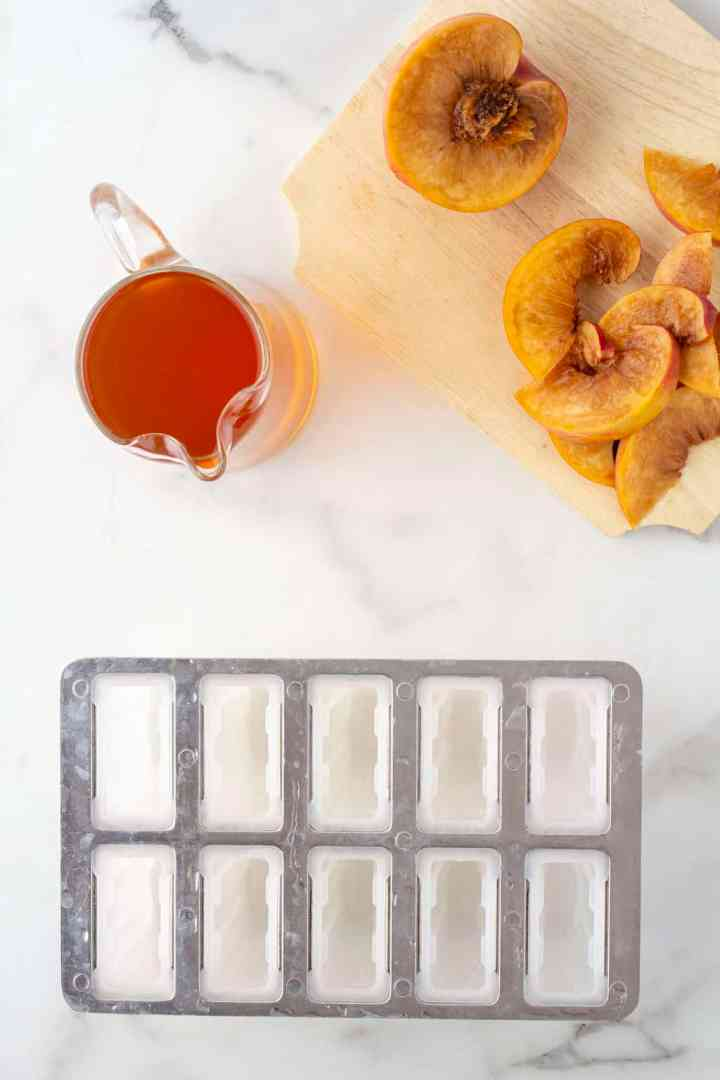 popsicle molds with sliced peaches