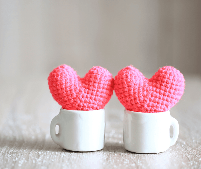 two tiny pink crocheted hearts in white cups