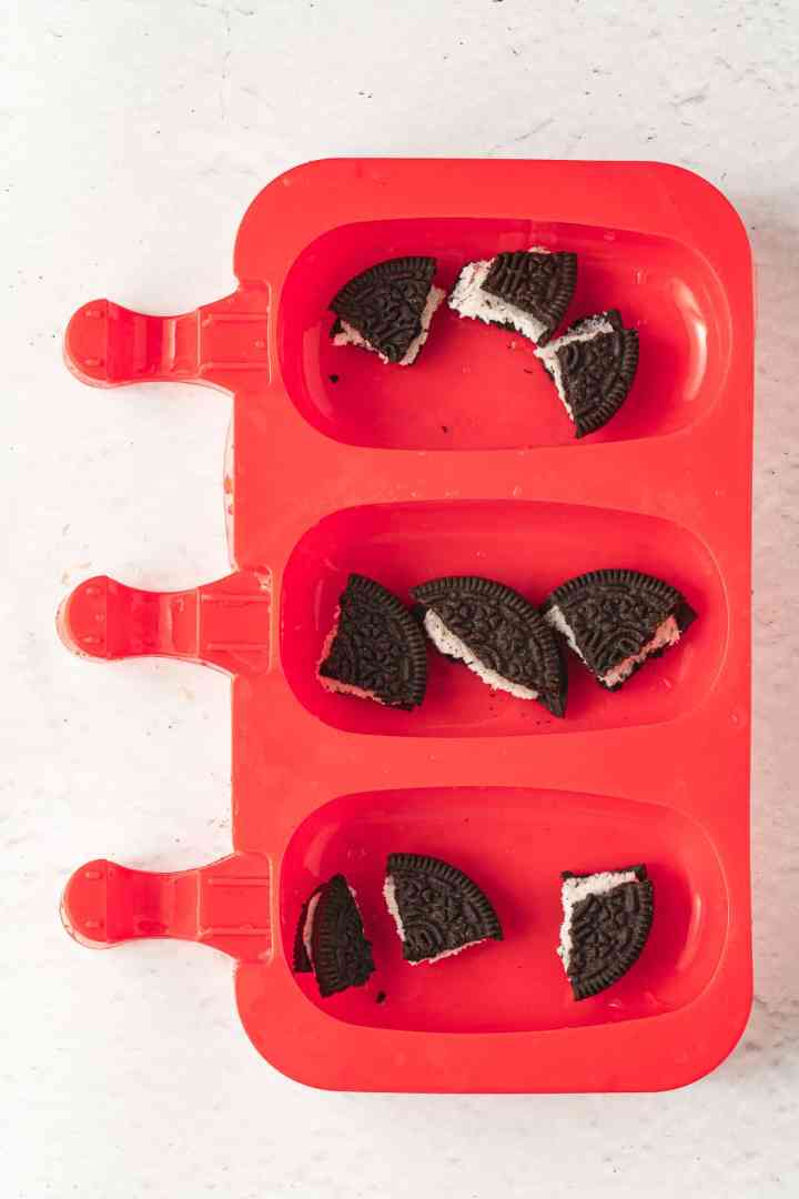 place Oreo cookies into the popsicle molds