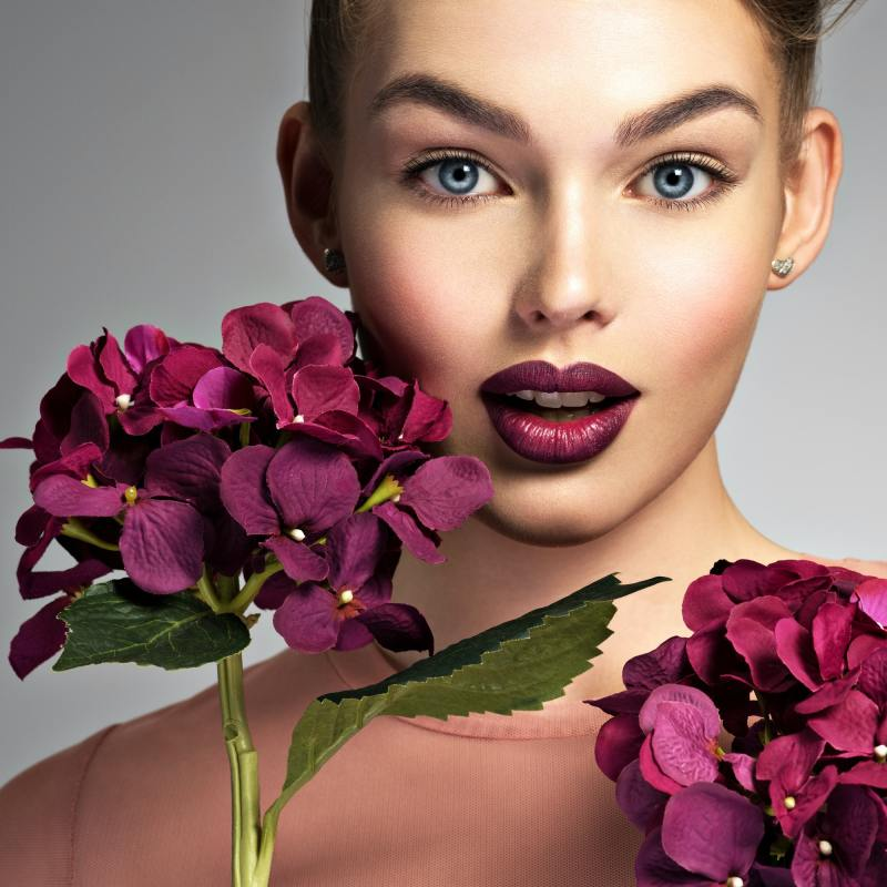 Girl with a creative hairstyle purple flowers.