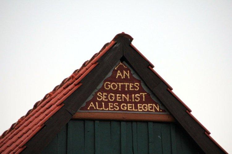 """Aufschrift """" An Gottes Segen ist alles gelegen"""" an der Seite eines Hauses."""