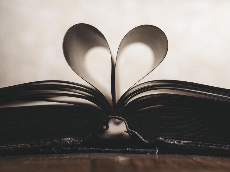 """Symbolbild zur Jahreslosung 2017: """"Gott spricht: ich schenke euch ein neues Herz und lege einen neuen Geist in Euch."""" - Hesekiel 36,26: Bild einer offenen Bibel, die Seiten bilden ein Herz"""