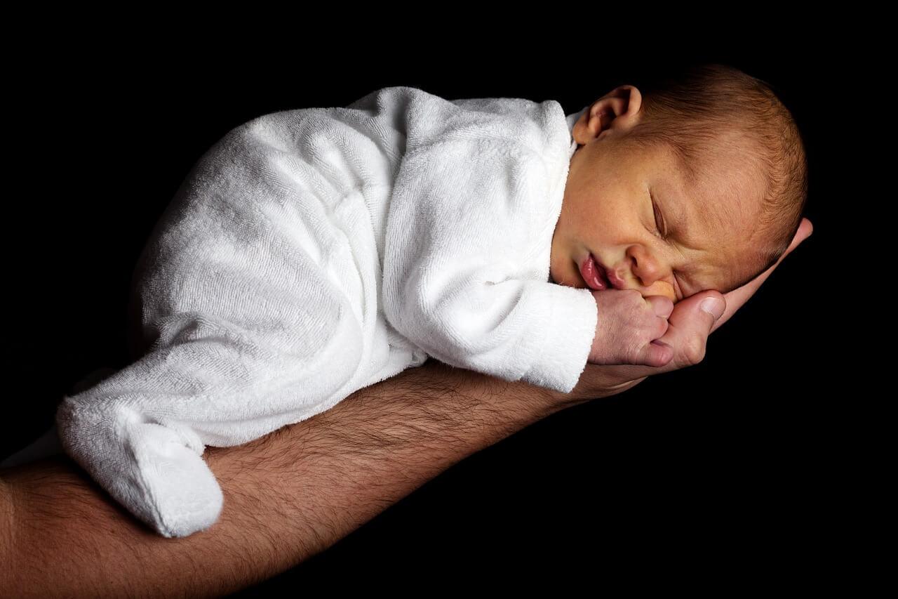 """Symbolbild """"Halten, nicht fallen"""": Baby in der Hand"""