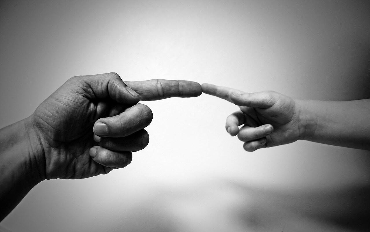 """Eine große und eine kleine Hand, deren Zeigefinger sich berühren. - Symbolbild """"Aber Gottes Hilfe habe ich erfahren bis zum heutigen Tag und stehe nun hier und bin sein Zeuge bei Klein und Groß. Apostelgeschichte 26, 22"""""""