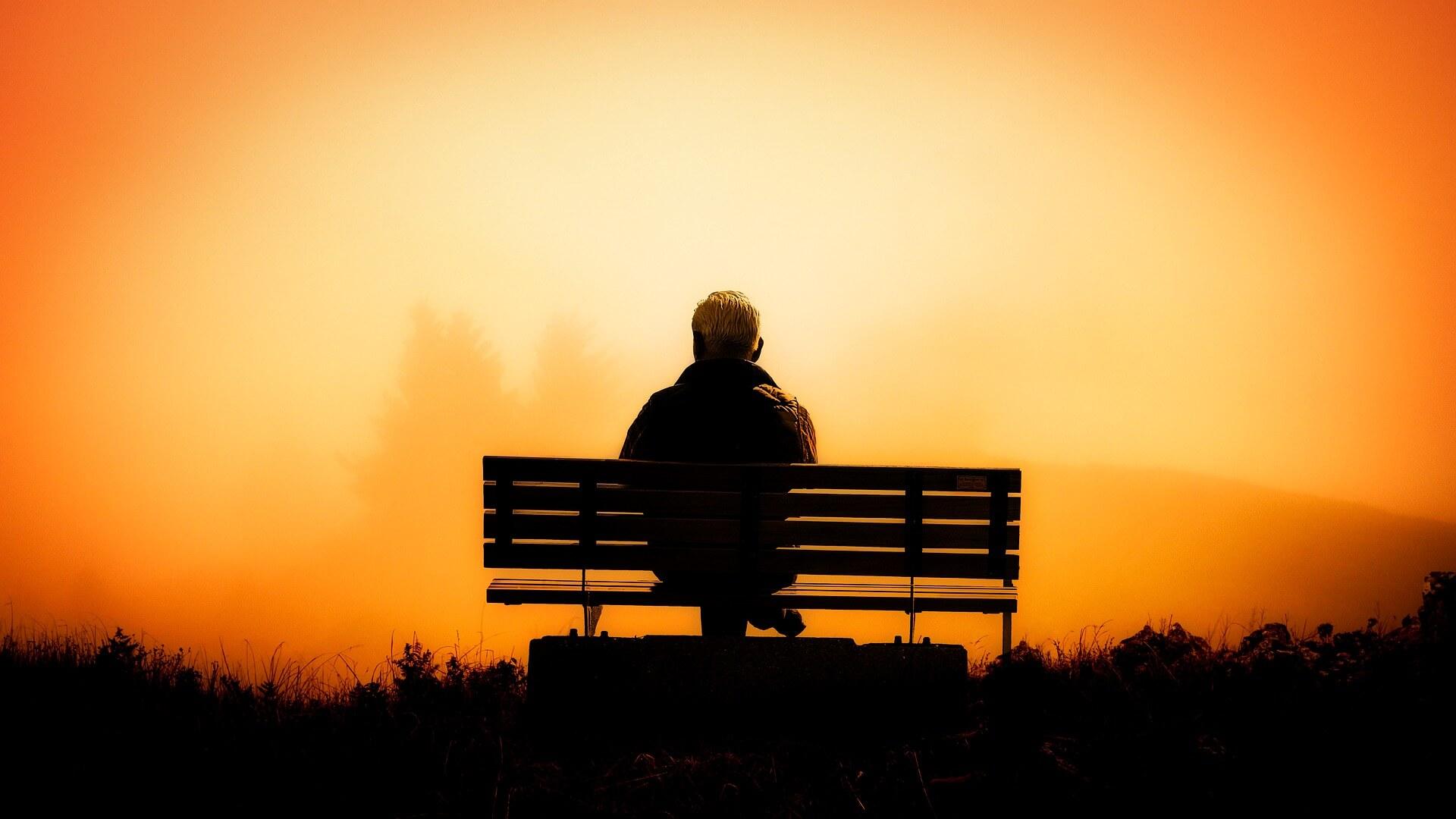 Symbolbild : Herausforderung Angenommen: Mann auf Bank vor Sonnenuntergang