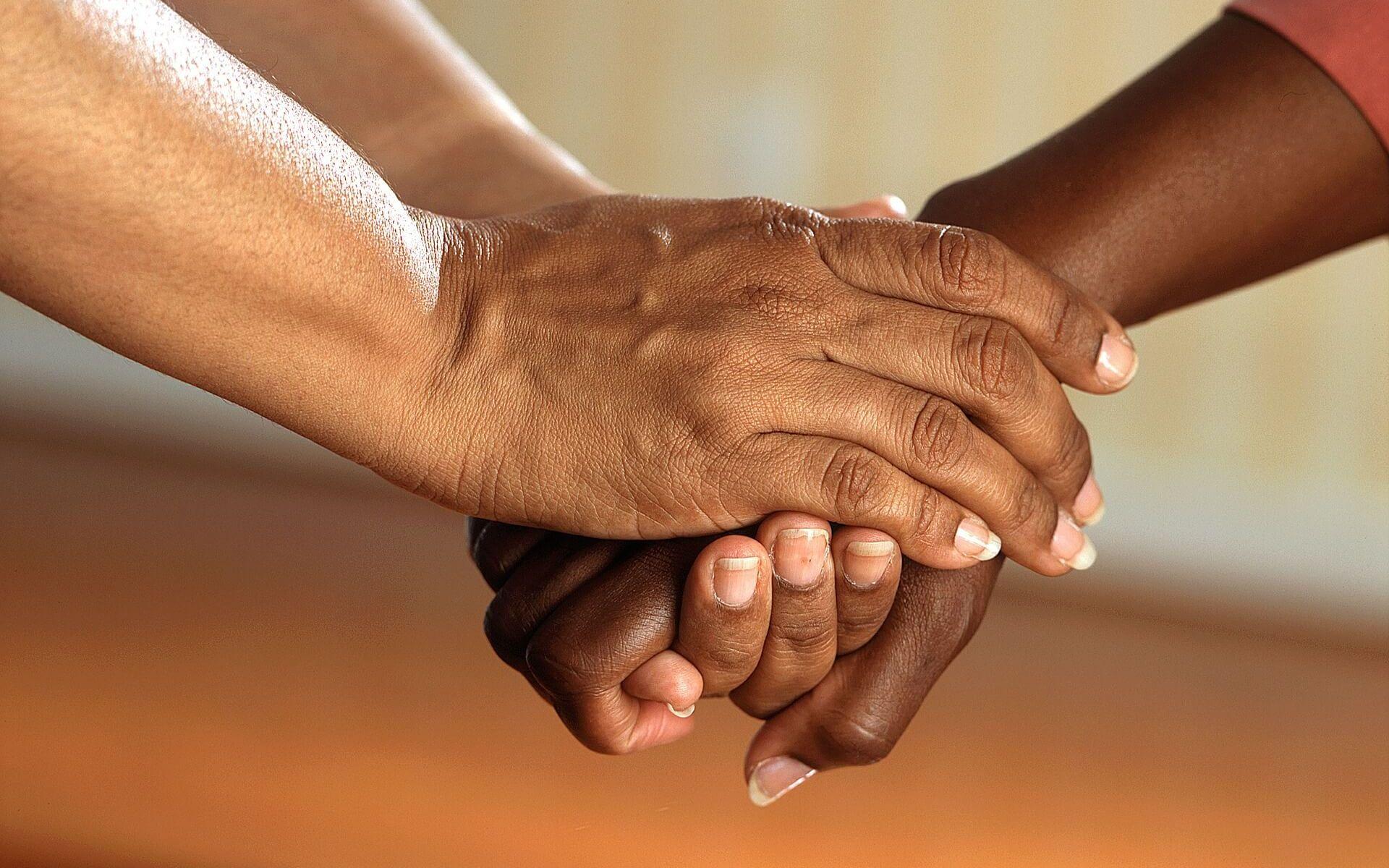 Zwei Menschen reichen sich die Hände.