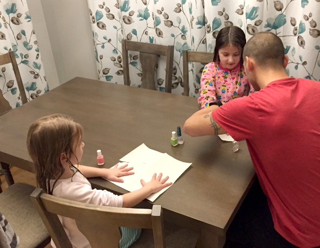 dad painting daughters nails