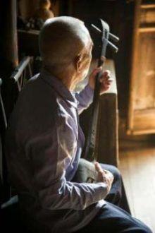 Anciano toca su guitarra en Daxu cerca de Guilin