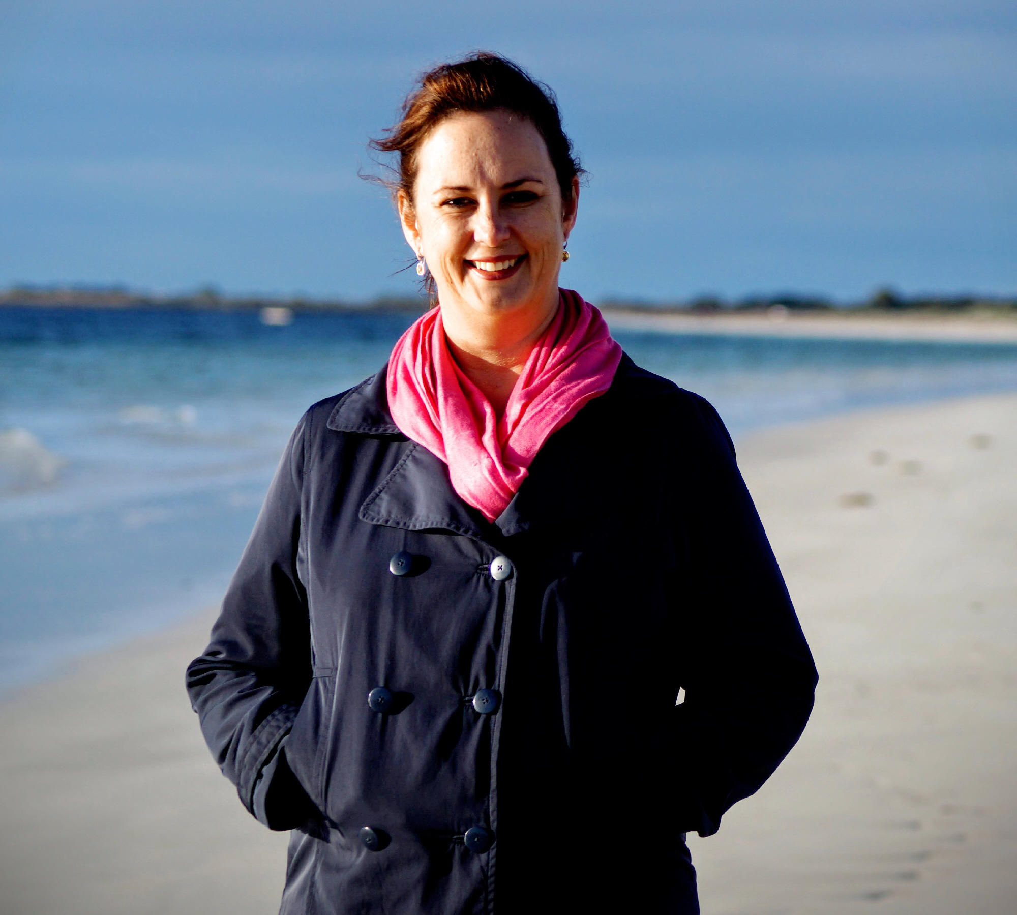 PR expert Felicity Moore stands smiling on a beach. Felicity wears a dark blue jacket and pink scarf.