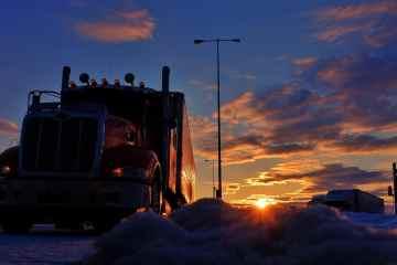 caminhão parado em frente ao por do sol.