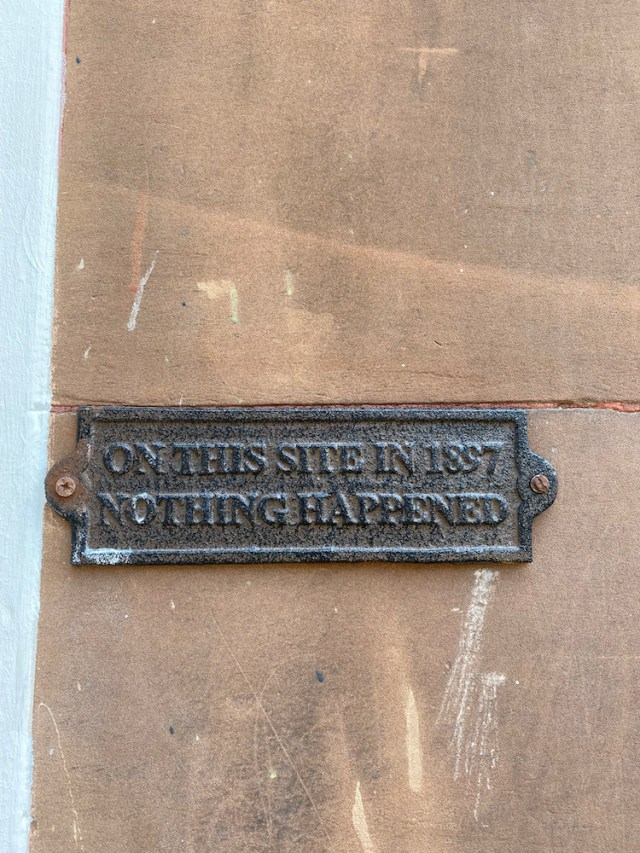 Plaque on a wall saying On This Site in 1897 Nothing Happened
