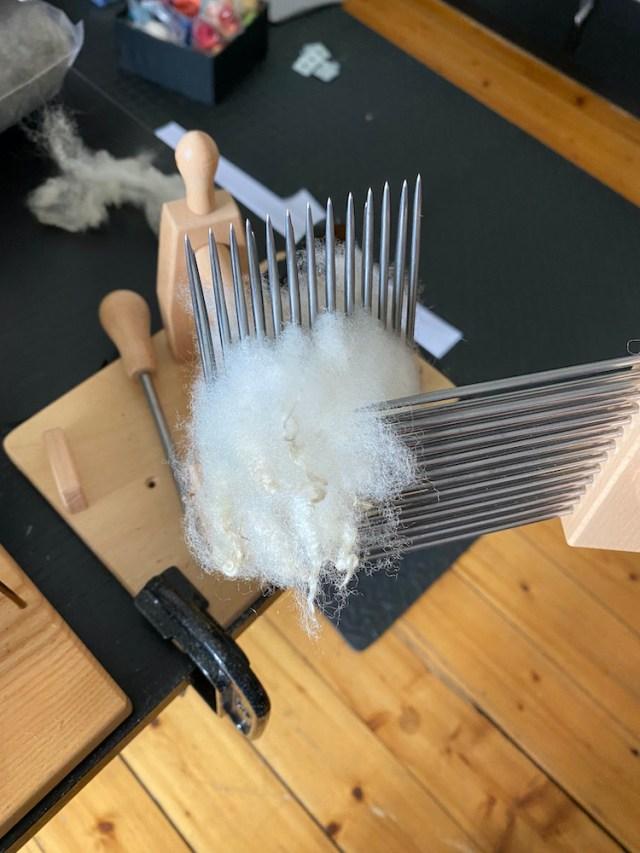 Eleanor Shadow uses English wool combs to process some wool locks