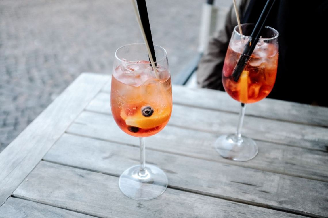Aperol spritz cocktail served in a wine glass.