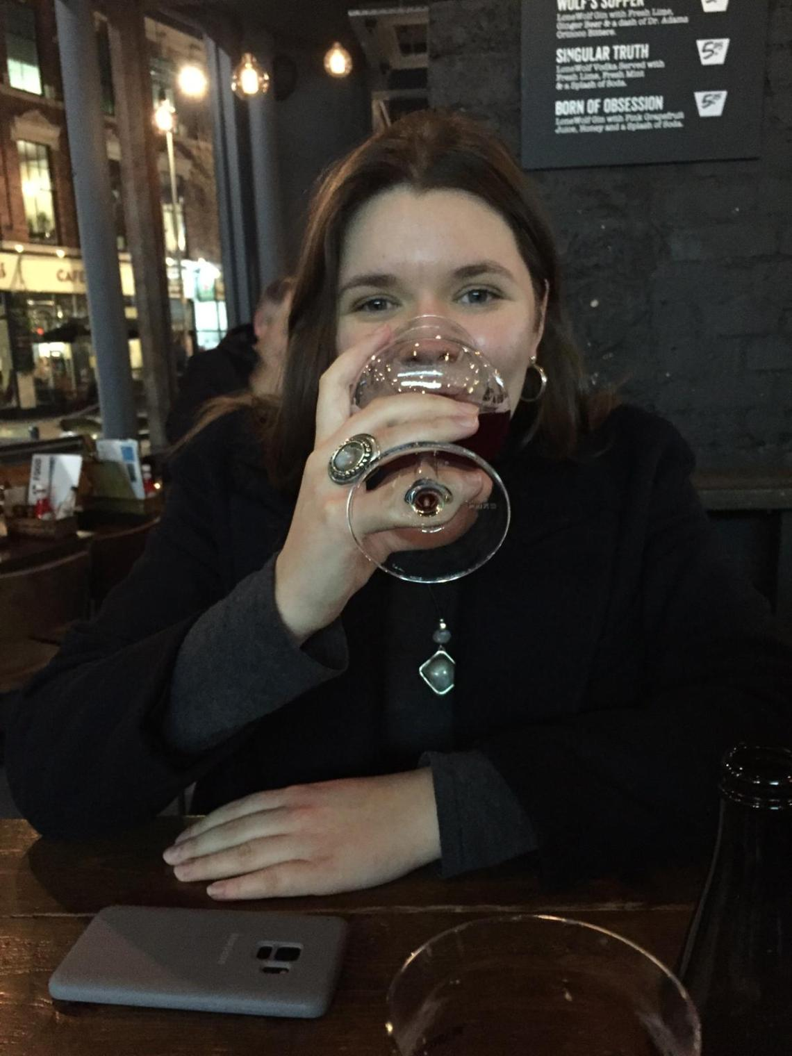 A young woman drinking a glass of beer at Brewdog Birmingham.