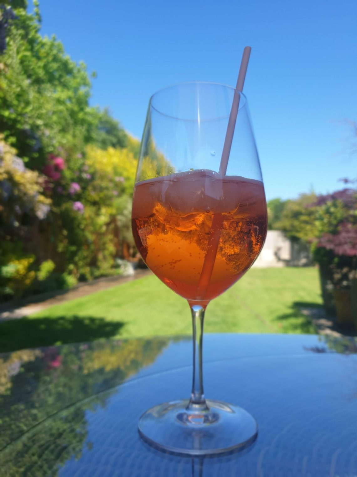 Aperol Spritz cocktail with Fever Tree Tonic, Prosecco and a garden background.