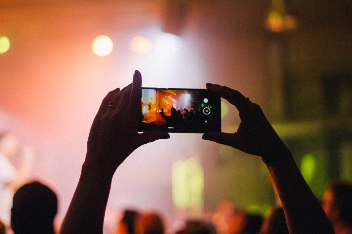 Find new music at a live music concert. Mobile phone taking a photo of live music.
