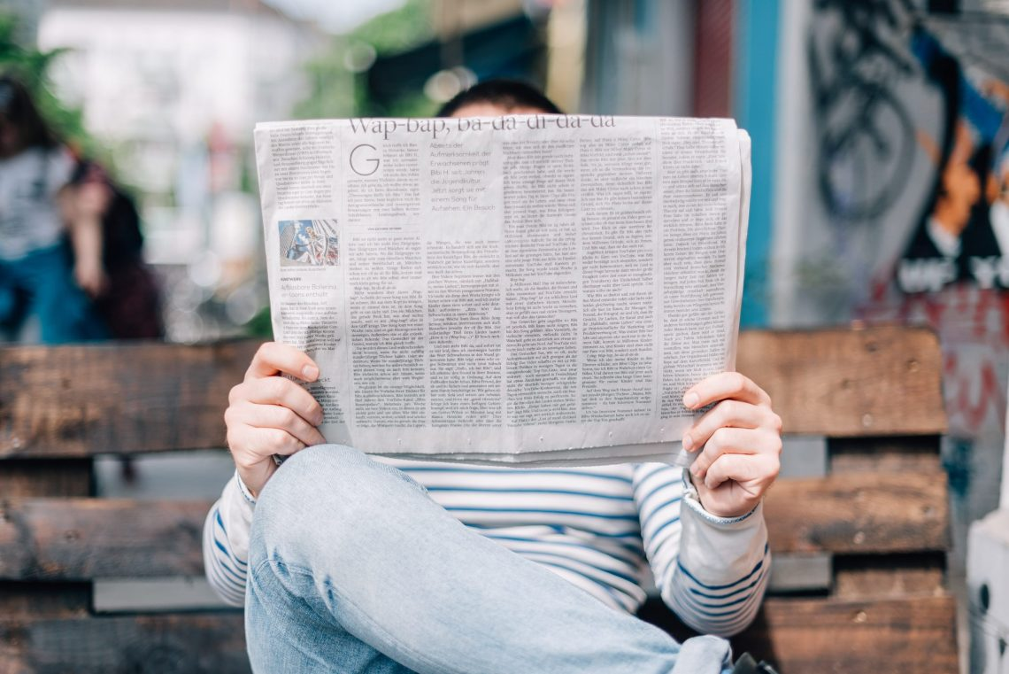 Find new music reading reviews. Man sat reading a newspaper.