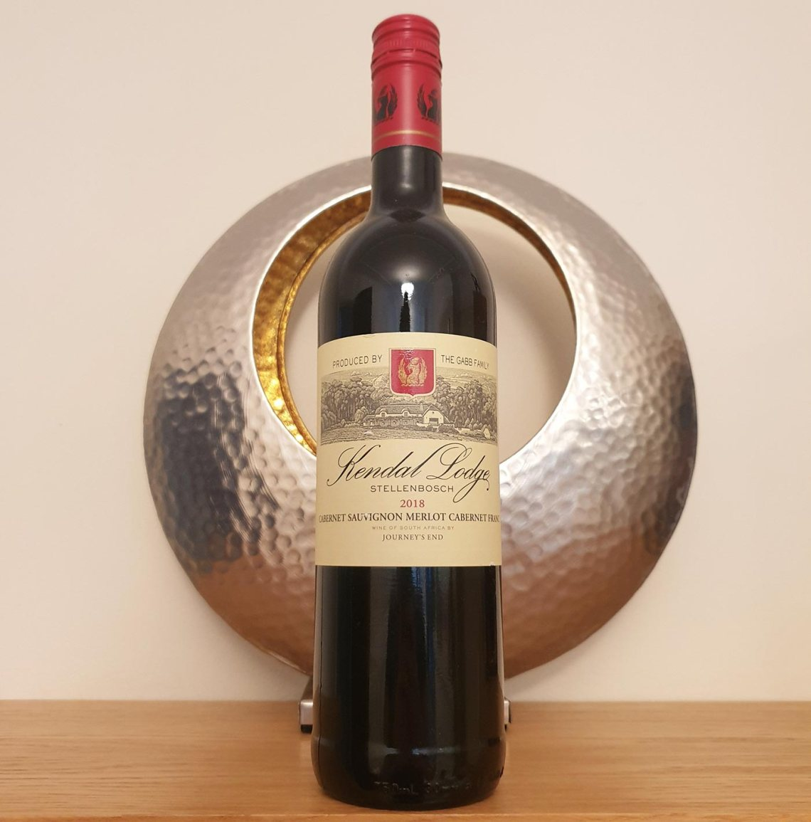 Bottle of Kendal Lodge red wine in front of a round metallic candle holder.