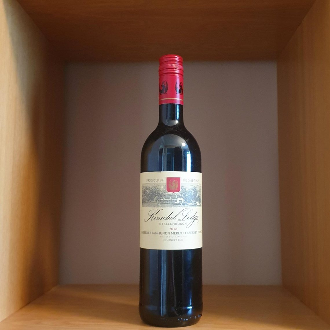Bottle of Kendal Lodge red wine sitting in the middle of a wooden shelf.