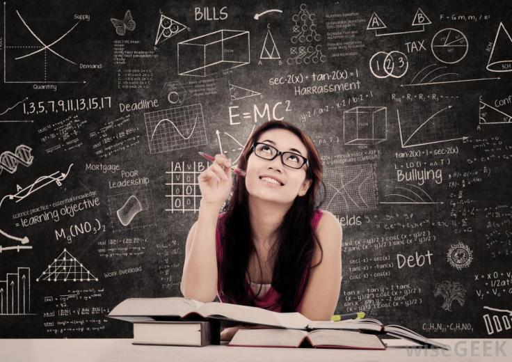 woman-in-glasses-with-chalkboard-of-equations-in-background