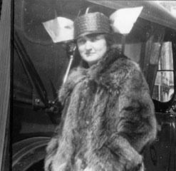 Ein original schwarz weiß Foto von Elizabeth Marston im dicken Mantel vor einem Auto.