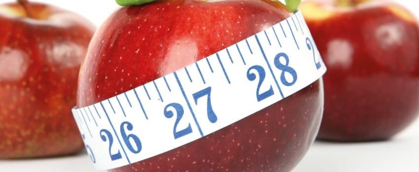 Ein Apfel und ein Maßband mit 1cm-Intervallen.